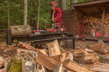 Older man using log splitter near a wood shed