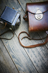 Old retro film analogue camera and belt bag (leather case) on vintage wooden boards.