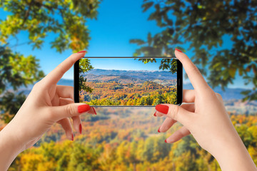 Girl taking photo with smartphone, autumn colorful landscape in background