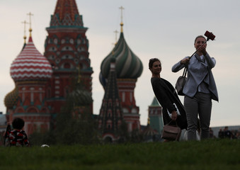 Women take a selfie with St. Basil's Cathedral in the background, at the newly opened Zaryadye Park off Red Square in central Moscow