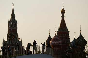 People take pictures at the newly opened Zaryadye Park off Red Square, with the Spasskaya Tower and St. Basil's Cathedral seen in the background, in central Moscow