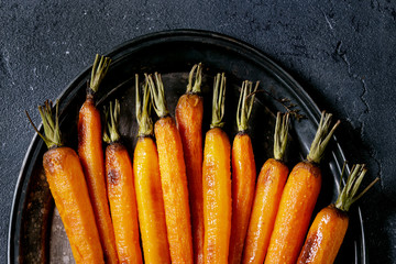 Roasted young whole carrot served on vintage metal tray over black texture background. Top view with space. Close up