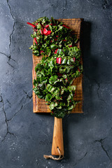 Cutting fresh chard mangold salad on wooden chopping board over black texture background. Top view with space