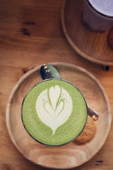 Matcha green tea latte art on wooden table.