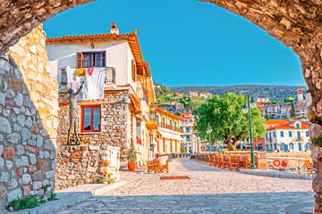 View on old medieval Greek city Nafpfktos Though arch in ancient medieval castle wall, popular and famous travel landmark. Nafpaktos is popular European travel destination. Old houses on embankment.