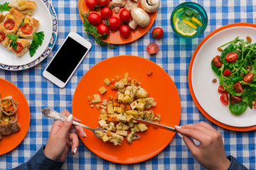 Woman eating healthy food on checkered tablecloth background, top view.