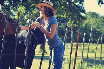 Wall Mural - Cowgirl petting cows in the pasture with authentic smile.