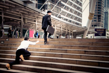 Smart Businessman is walking on the steps and heading to his goal. Competition between big and small business. Another competitor try to climb on the step to and cannot follow up him