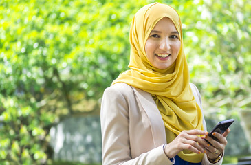 Happy young muslim woman holding a phone while looking out like thnking of good memories