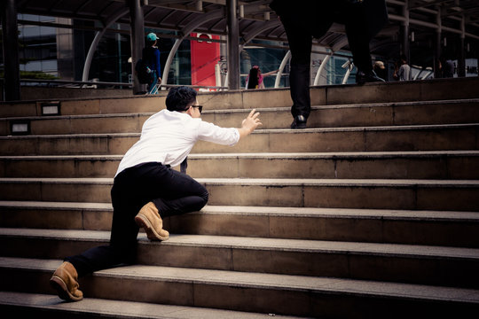 Competitor try to climb on the step to follow up smart Businessman who is walking on the steps and heading to his goal. Competition between big and small business.