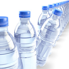 Row of plastic bottles with clear drinking water and blue caps, isolated on white background