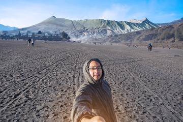 A Asian young man attractive backpacker tourist taking selfie photo and adventure on vacations route at Volcano Rinjani, Indonesia.