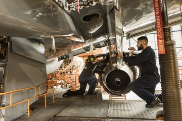 Aircraft maintenance engineers examining turbine engine of