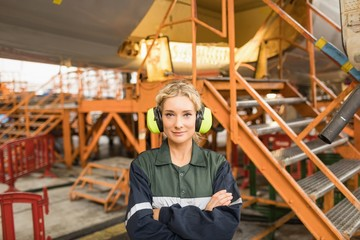 Male aircraft maintenance engineer standing with arms crossed at