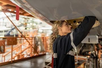 Female aircraft maintenance engineer working over an aircraft