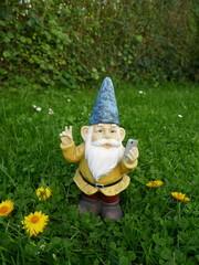 """Gartenzwerg macht ein """"Peace-Selfie"""" auf einer grünen Wiese mit gelben Blumen"""