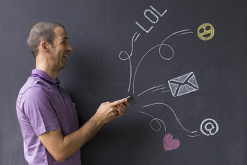 Concept of social media chat. Single white adult man standing in front of a blackboard using his smart phone.