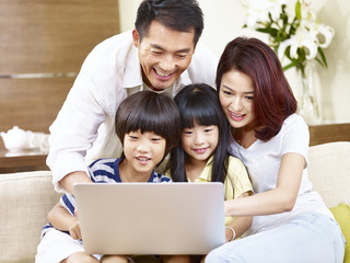 asian family with two children using laptop together