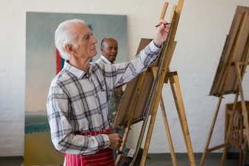 Side view of senior man painting on easel
