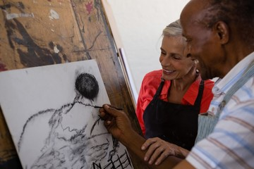 Senior woman assisting man while painting on paper