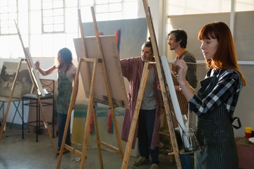 Adult students painting on canvas