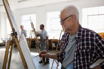 Senior males painting in art class