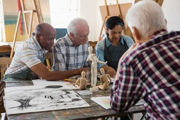 Senior friends discussing over painting while sitting at table