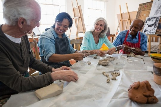 Smiling senior friends making clay products