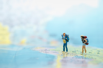 Travelling concepts. Two of traveler miniature mini figures with backpack standing on map