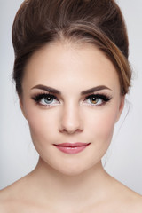 Portrait of young beautiful stylish smiling girl with hair bun and winged eyes make-up