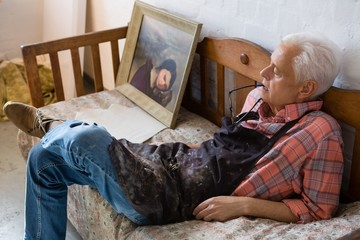 High angle view of senior artist relaxing on sofa