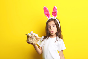 Beautiful little girl with rabbit ears and easter eggs on yellow background