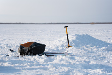 Ski, backpack and shovel in the snow