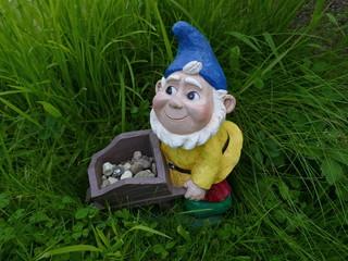 Gartenzwerg mit einem blauen Hut, gelber Jacke und einer Schubkarre voller Kieselsteine