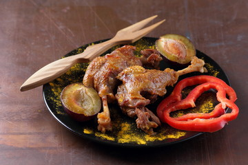 Fried meat with plums and red bell pepper on a black plate with a wooden fork on a rusty background