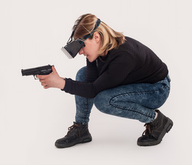 Woman play VR shooter game with vr glasses and gun