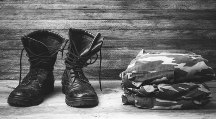old leather black mens boots ankle boots and a military uniform on wooden background front view closeup photo