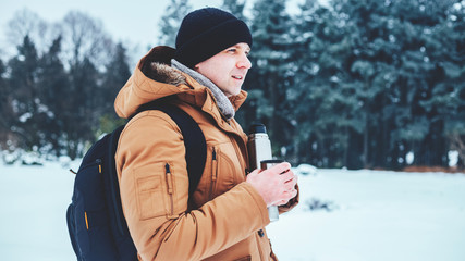a young man in a red jacket with a backpack standing on the snow and holding a thermos and a mug of tea. Winter forest.