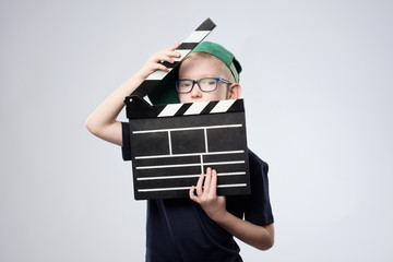 boy in green hat holding clapper board in hands.