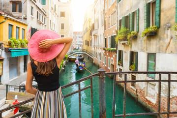 Frau mit rotem Sonnenhut schaut auf einen Kanal mit Gondel in Venedig, Italien Fototapete