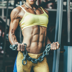 Muscular female in sports clothing holding chains in hands at gym