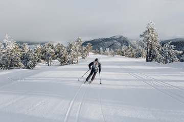 view from behind of a mountain skier having fun skiing in a snowy ski resort