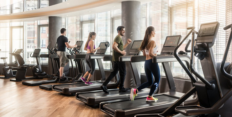 Deurstickers Fitness Group of four people, men and women, running on treadmills in modern and luminous fitness gym