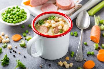 White enamel mug with delicious homemade pea soup with sausage and croutons. Healthy food concept.