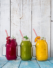 Healthy fresh smoothies with ingredients on old wooden table.