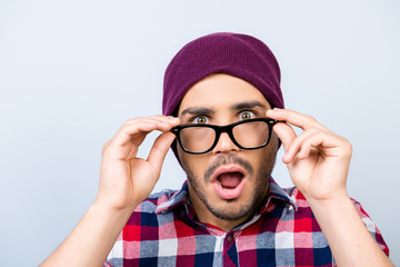 Close up portrait of amazed guy hipster in checkered shirt, holding his trendy glasses, he is shocked, with wide open eyes and mouth on pure background