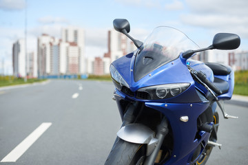 Outdoor pciture of custom-built motorcycle parked on road against blue sky and modern high-rise buildings background. Motorcycling, transport, transportation, lifestyle, extreme and hobby concept