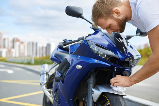 Cropped outdoor portrait of handsome bearded young European man cleaning blue motorcycle using white microfiber cloth, standing on empty parking lot with urban setting in background. Valeting concept