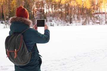 Back view of unrecognizable male in hat and cout with fur hood carrying stylish backpack taking picture of amazing winter landscape using copyspace mobile phone while walking alone on sunny day