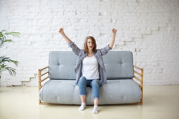 Youth, leisure, fun and happiness. Happy young causally dressed female sitting on grey sofa in living room, keeping arms raised, feeling excited, watching TV, cheering for her favorite football team